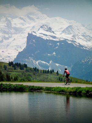 Velovation clients riding past the lake at the top of the col de Joux Plane with Mont Blanc in the background